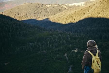Rear view of female traveler looking at green mountains, Carpathians, Ukraine