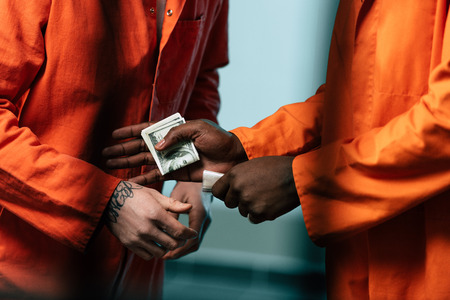 Cropped image of prisoner buying drugs at African american inmate Stock Photo