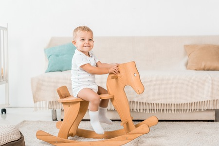 Adorable smiling toddler sitting on toy wooden horse 写真素材
