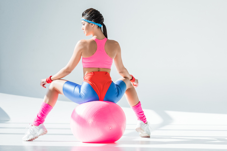 Back view of athletic young woman sitting and exercising on fitness ball on grey