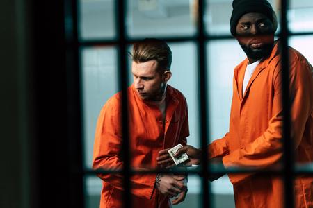 Prisoner buying drugs at African american inmate in prison room