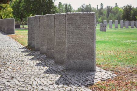 Selective focus of identical headstones placed in row at cemetery