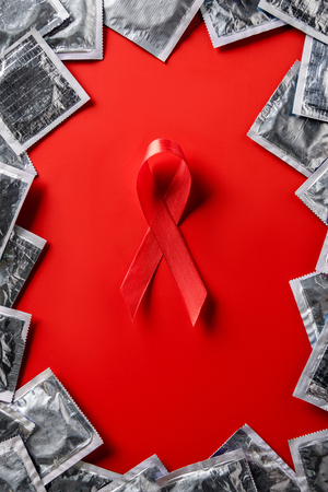 Top view of aids awareness red ribbon and silver condoms on red background