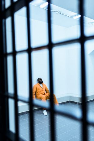 African american prisoner sitting on bench in prison cell Banco de Imagens