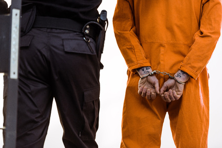 Cropped image of prison guard leading criminal in handcuffs