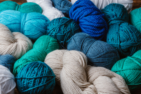 Close up view of white, blue and green yarn for knitting as backdrop