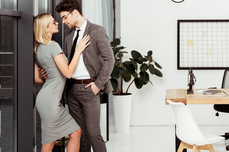 Side view of young business colleagues flirting in office Zdjęcie Seryjne