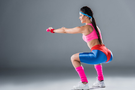 Side view of sporty girl doing squats with dumbbells on grey