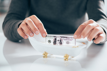 Cropped shot of man washing dollar banknote in tub, money laundering concept