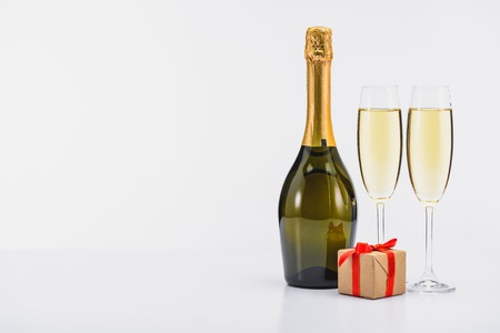 Close up view of bottle and glasses of champagne with wrapped gift on white background 写真素材