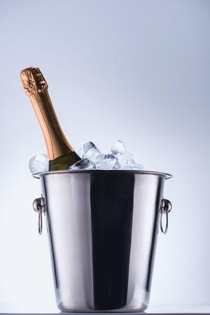 Vista de cerca de una botella de champán en un balde con cubitos de hielo sobre fondo gris