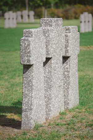 Close up view of identical memorial stone crosses placed in row at cemetery