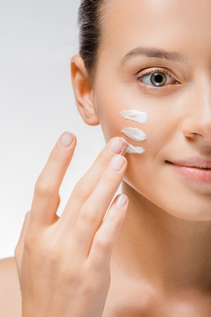 Young beautiful woman applying white cream with fingers on cheek