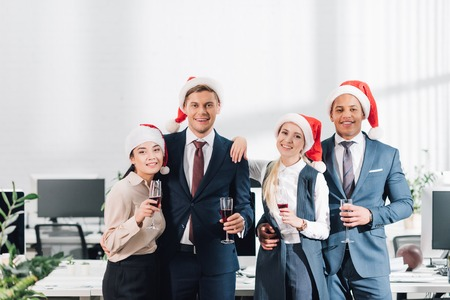 Happy young colleagues in Santa hats drinking champagne and smiling at camera while celebrating xmas in office Stock Photo