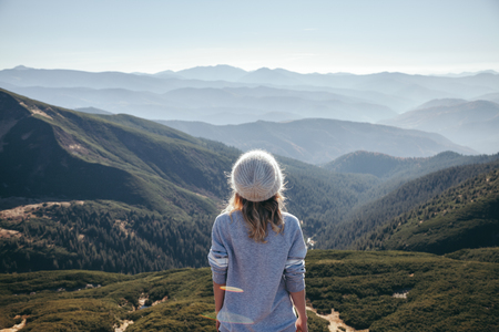 rear view of female traveler looking at scenic mountains on sunny day, Carpathians, Ukraine Imagens