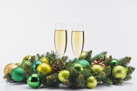 close up view of glass of champagne and festive christmas wreath on white backdrop