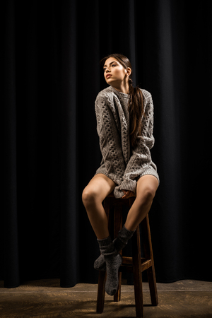 beautiful woman in woolen grey sweater and socks sitting on bar stool on black background Stock Photo