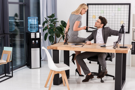 Young businesswoman pulling colleagues tie while sitting on table in office, office romance concept