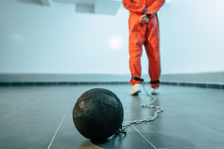 Back view of prisoner in orange uniform with weight tethered to leg