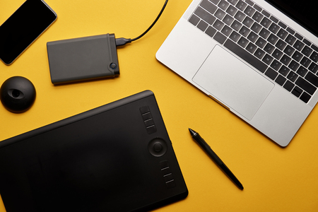 Top view of various graphic designer gadgets on yellow surface