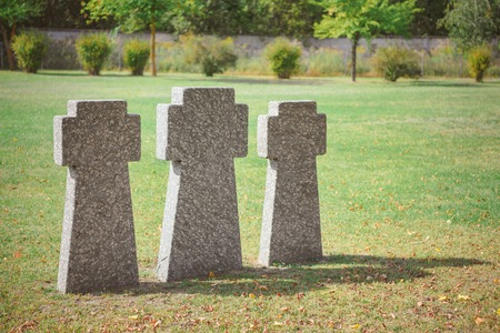 Selective focus of memorial stone crosses placed in row on grass at graveyard