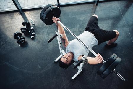 Draufsicht auf konzentriertes Sportlertraining mit Langhantel im Fitnessstudio