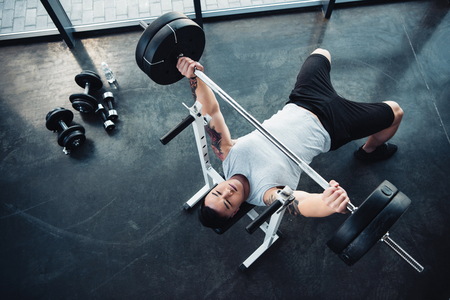 Top view of concentrated sportsman training with barbell at gym Stok Fotoğraf