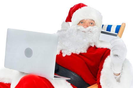 santa claus shopping online with laptop and credit card isolated on white
