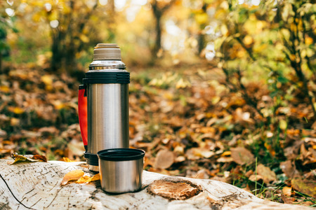 metallic camping thermos on beautiful autumnal background
