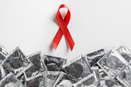 top view of aids awareness red ribbon and silver condoms on white background, medical concept Stockfoto