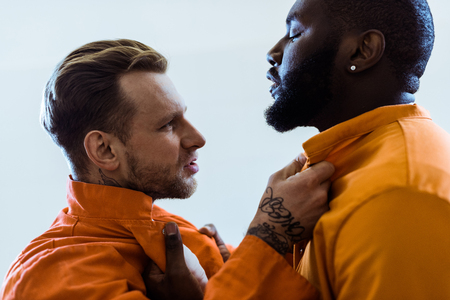 side view of multiethnic prisoners threatening each other and holding collars Stock Photo
