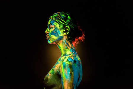 Side view of woman painted with colorful ultraviolet paints on black backdrop Foto de archivo - 112345424