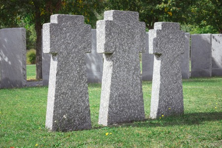 Selective focus of memorial stone crosses placed in row at graveyard