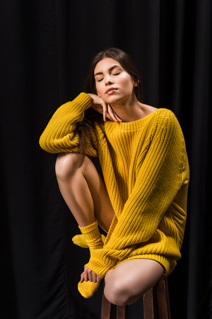 Woman in yellow woolen sweater with eyes closed sitting on bar stool on black backdrop Stock Photo