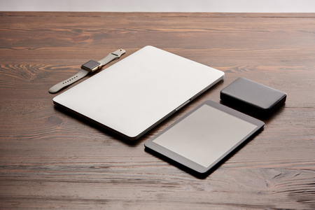 Laptop with tablet, smart watch and portable HDD on wooden table