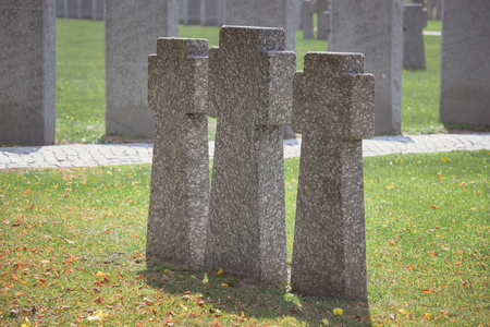 Selective focus of identical old memorial headstones placed in row at cemetery