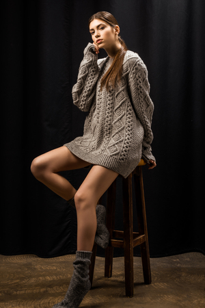 Beautiful young woman in woolen grey sweater on bar stool on black background Archivio Fotografico - 112345457