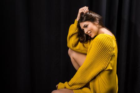 side view of beautiful woman in yellow woolen sweater on black backdrop Archivio Fotografico - 111784724