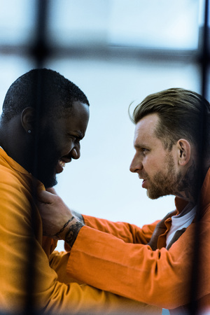 Side view of multiethnic prisoners threatening each other and holding collars Stock Photo - 112345477
