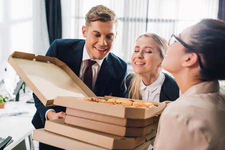 Happy young business colleagues smelling tasty pizza in office