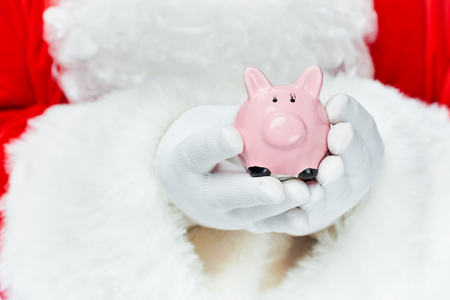 Cropped view of Santa Claus holding piggy bank Stock Photo