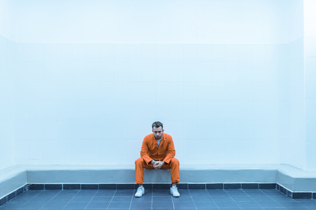 Prisoner sitting on bench in prison room Banco de Imagens - 112345571