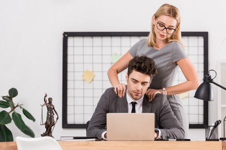 Businesswoman making massage to colleague at workplace in office, office romance concept Zdjęcie Seryjne