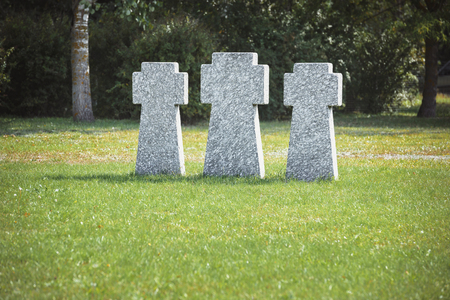 Memorial stone crosses placed in row on grass at graveyard