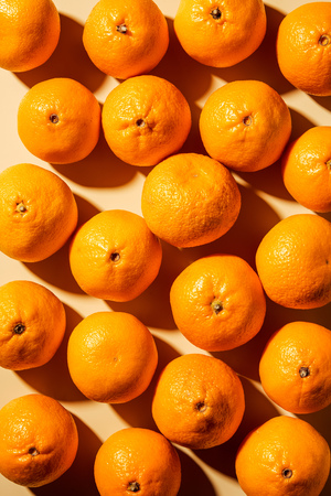 Top view of arranged fresh wholesome tangerines on beige background