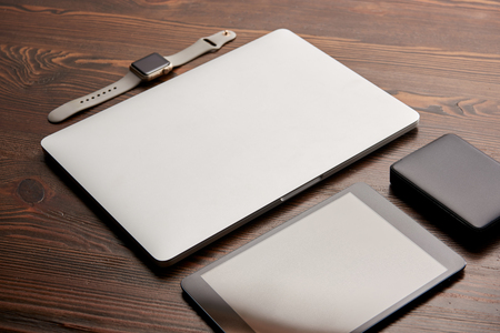 Close-up shot of laptop with digital tablet, smart watch and portable HDD on wooden table Stock Photo