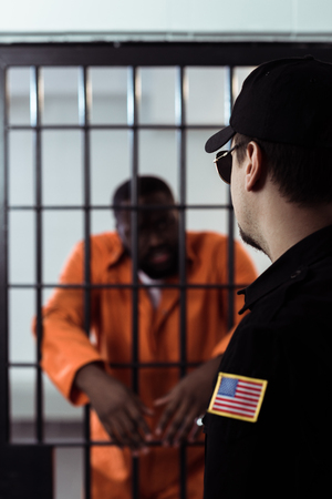 Security guard standing near prison bars and looking at African american prisoner Banco de Imagens