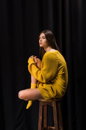 Side view of thoughtful woman in yellow woolen sweater sitting on bar stool on black backdrop
