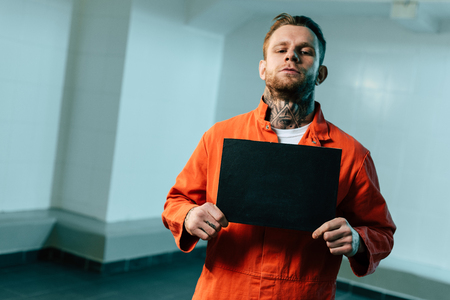 Prisoner holding blackboard and looking at camera Stock Photo