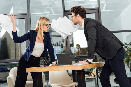 passionate businesswoman throwing papers away while looking at businessman at workplace, office romance concept Stok Fotoğraf